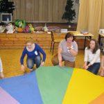 Zabawa z chustą - studentki i prowadząca kucają przy rozciągniętej kolorowej chuście