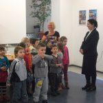 Grupa przedszkolaków z opiekunem Martę Falińską oraz kanclerz Zofia Kozioł w auli budynku przy ul. Szerokiej 9