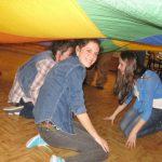Studentki klęczą na podłodze nakryte chustą animacyjną