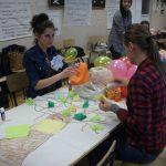 Studentki siedzą przy stole pełnym materiałów plastycznych i nadmuchanych baloników
