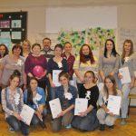 Grupowe zdjęcie uczestników warsztatów - studentki prezentują otrzymane dyplomy