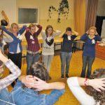 Grupa uczestników warsztatów stoi w kole z rękami założonymi za głowę