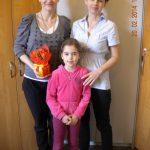 Dwie pracownice Działu Personalnego pozują do zdjęcia z dziewczynką z grupy przedszkolaków