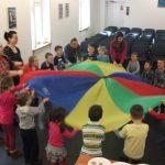 Dzieci w trakcie zabawy z kolorową chustą, zorganizowanej przez studentki z koła naukowego