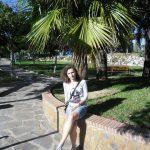 Studentka siedzi na obmurowaniu gazonu w gaju palmowym
