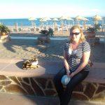 Studentka siedzi na niskim murku na plaży, w tle morze