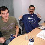 Dwóch studentów z Turcji siedzi przy biurku, jeden z nich trzyma koszulkę z logo Uczelni