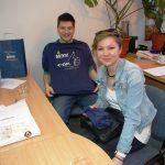 Studentka i student z Chorwacji przy biurku w pokoju Katedry Zarządzania, student trzyma rozłożoną koszulkę z logo MWSE