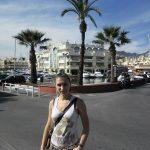Studentka stoi na ulicy, w tle domy i rosnące palmy