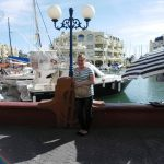 Studentka pozuje na tle łodzi zacumowanych w porcie