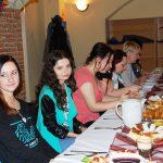 Studenci siedzą przy zastawionym stole