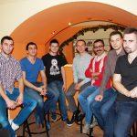 Grupa siedmiu mężczyzn pozuje do zdjęcia siedząc na krzesłach barowych