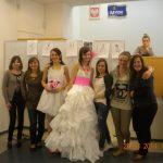 Grupa siedniu studentek pozuje do zdjęcia, dwie z nich przebrane są w suknie ślubne