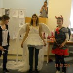 Studentki w strojach anioła i diabła obok nich projektantka omawiająca stroje
