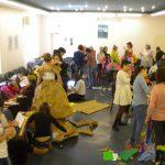Studenci w auli w trakcie wykonywania strojów, na podłodze materiały