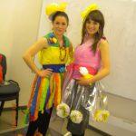 Dwie studentki przebrane w róznokolorowe sukienki, we włosach duże żółte kwiaty