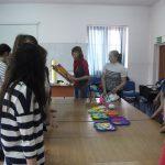 Uczestnicy warsztatów plastycznych stoją przy stole, na którym położone prace