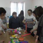 Uczestnicy warsztatów plastycznych stoją przy stole - prowadzący objaśnia zadanie