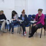 Cztery studentki siedzą w sali wykładowej, pisząc coś na rozłożonych blatach dołączonych do krzeseł