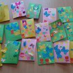 Kartki świąteczne wykonane przez dzieci. Na kartkach z zielonego i rózowego kartonu naklejone motyle kurczaki i tulipany