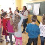Grupa dzieci stoi w sali lekcyjnej, na środku studentka prowadząca zajęcia