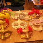 Na stole leżą maski wykonanane przez uczestników