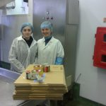 Dwie pracownice w strojach ochronnych przy pudełkach kartonowych przeznaczonych do pakowania towarów