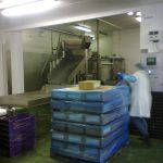 Hala produkcyjna, pracownik w białym fartuchu przy zapakowanej palecie z towarami