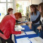 Uczestnicy warsztatów w trakcie rejestracji przy stole ustawionym w holu budynku