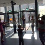 Studentki pedagogiki i dzieci stoją w okręgu w trakcie zabawy w holu teatru
