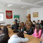 Uczniowie szkół średnich siędzący przy stołach w sali konferencyjnej. W tle mgr Karolina Chrabąszcz prowadzi prelekcję