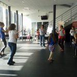 Studentki i dzieci w trakcie zabawy w holu teatru