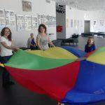 Studentki i dzieci trzymające rozłożoną kolorową chustę do zabawy