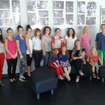 Zdjęcie grupowe - studentki stoją pod ścianą w holu teatru, dzieci siedzą