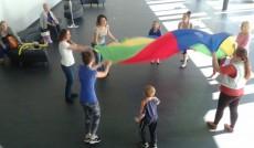 Studentki i dzieci w trakcie zabawy kolorową chustą - widok z góry