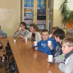 Dzieci siedzą przy stole i piją napój z kubków plastikowych