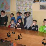 Dzieci podczas poczęstunku. Część dzieci pije z plastikowych kubków siedząc przy stole, część stoi za stołem