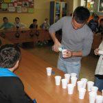 Student z Turcji rozlewający napój do stojących na stole kubków