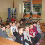 Uczniowie siedzą na krzesłach podczas prezentacji