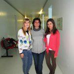 Dwie studentki z wykładowcą w korytarzu uczelnianym