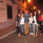 Grupa studentów pozuje stojąc na ulicy - wieczór
