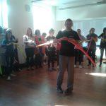 Prowadzący warsztaty stoi na środku sali i prezentuje uczestnikom sposób kształtowania balonu