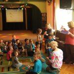 Dzieci przedszkolne siedzą na dywanie, Panie rozdają drobne upominki
