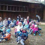 Dzieci i opiekunowie siedzą w grupie na trawie przy stodole