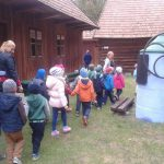 Dzieci i ich opiekunowie przechodzą przez podwórze , obok drewniany dom i studnia