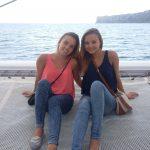 Dwie studentki siedzą, w tle morze