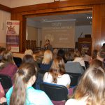 Sala wykładowa, przed sceną kanclerz mgr Zofia Kozioł wita zebranych