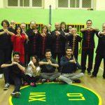 Grupa studentów stoi w sali gimnastycznej - trening Tai Chi