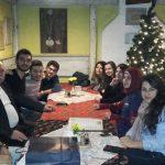 Studenci zagraniczni siedzą przy stole w tle choinka
