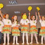 Dzieci (sześć dziewczynek i jeden chłopiec) w trakcie przedstawienia. Dziewczynki mają białe podkoszulki i zielono pomarańczowe spódniczki, unoszą w górę żółty znaczek z uśmiechniętą buzią
